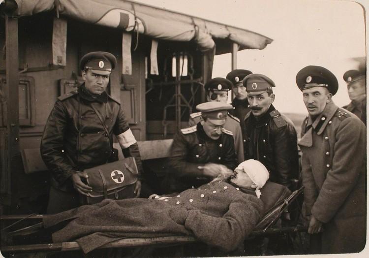 Врач и группа летчиков авиационной роты укладывают поручика Гринёва, потерпевшего аварию на своём биплане, на носилки для переноса в санитарный автомобиль после оказания ему первой помощи на аэродроме.
