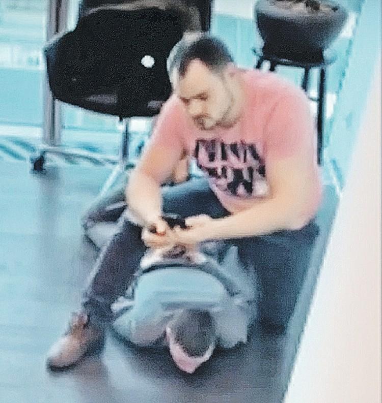 Кадр с камер видеонаблюдения: на полу лицом в пол лежит брокер со связанными за спиной руками. А на нем восседает тот самый посетитель. Фото: Кадр видеосъемки