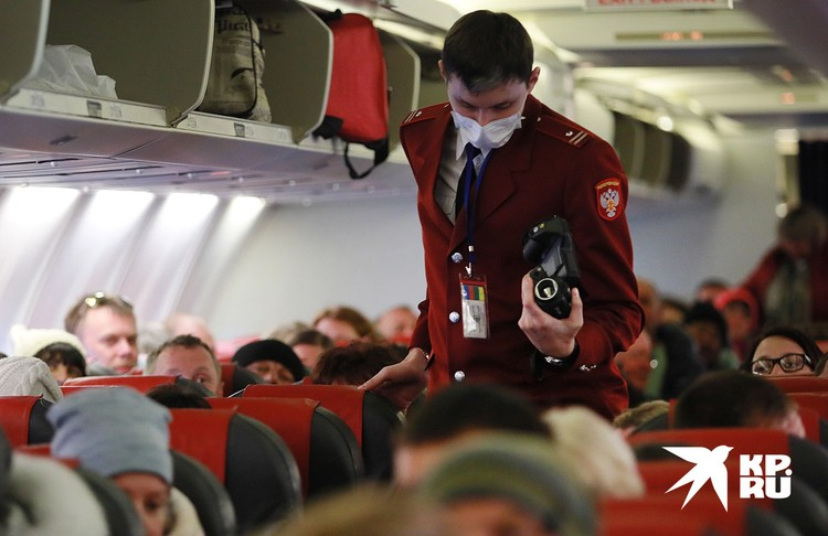 Проверка пассажиров сотрудником Роспотребнадзора в салоне самолёта.