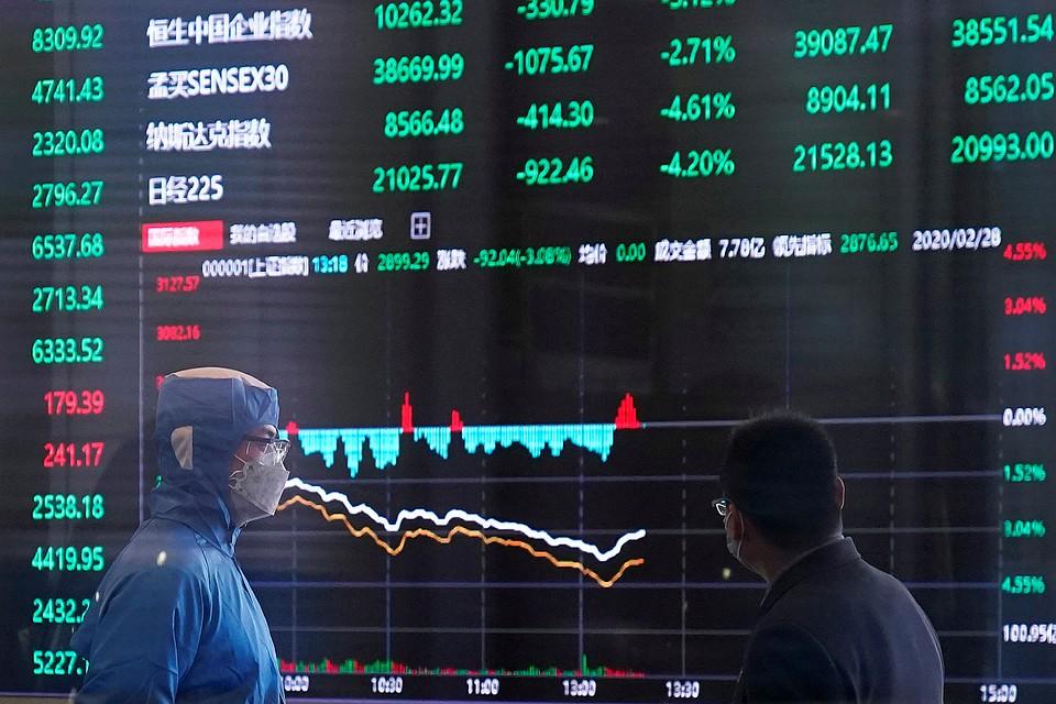 Трейдеры у табло шанхайской биржи наблюдают за падением котировок. Фото: REUTERS