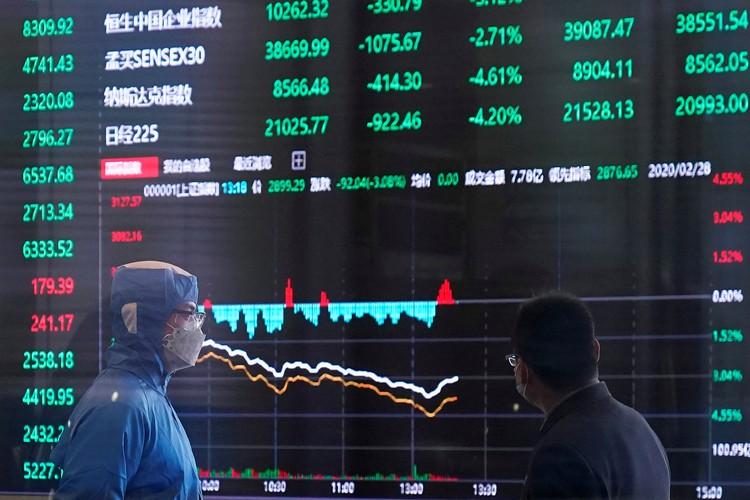 Трейдеры у табло шанхайской биржи наблюдают за падением котировок.