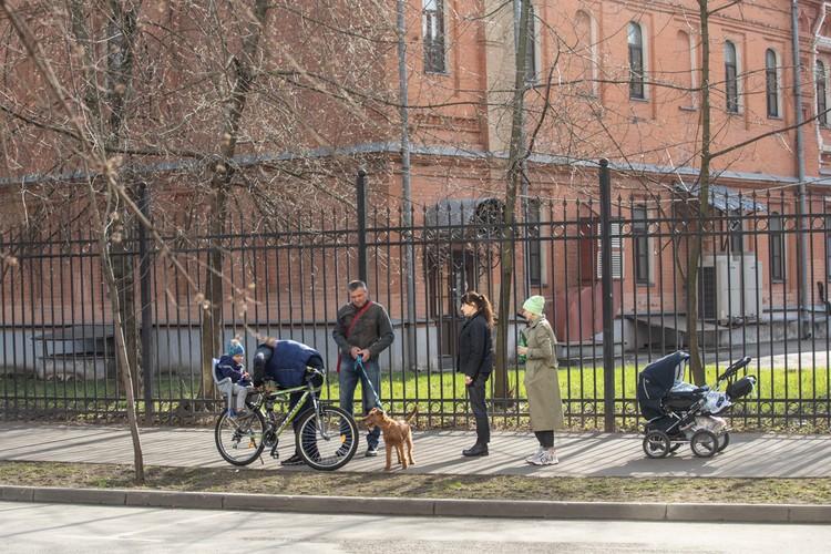 Люди выходят на прогулку в маленькими детьми.