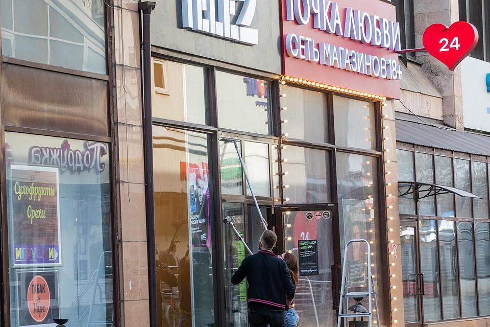 Продавцы секс-шопа и сотовой связи объединились, чтобы помыть общие окна. Фото: Андрей АБРАМОВ