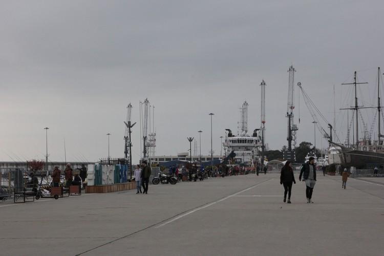 На набережной у яхтенной марины гуляют туристы