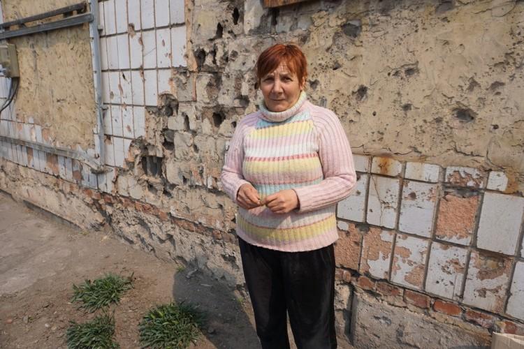Елена возле стены сельского магазина. Здесь все в следах от осколков.