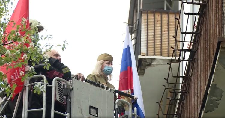 Чтобы поздравить ветерана с Днём Победы, сотрудники МЧС поднялись к его балкону в спасательной люльке. Фото: Пресс-служба МЧС России