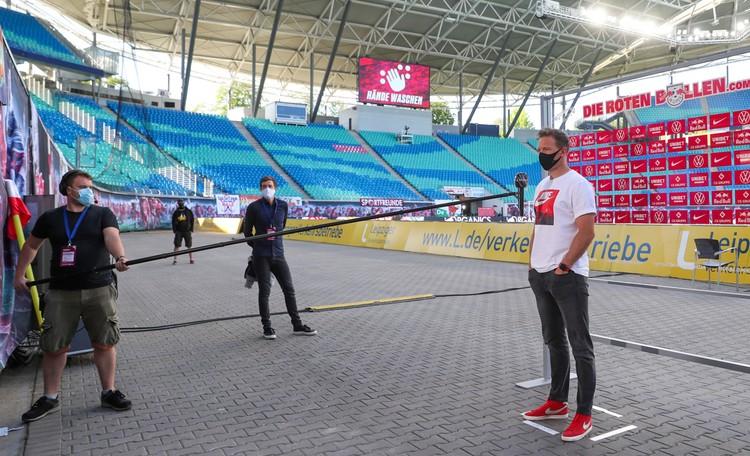 Вот так теперь в немецком футболе соблюдают дистанцию. На фото тренер «Лейпцига» Юлиан Нагельман дает интервью после матча, в котором его команда, претендующая на медали, не смогла дома обыграть «Фрайбург» (1;1).