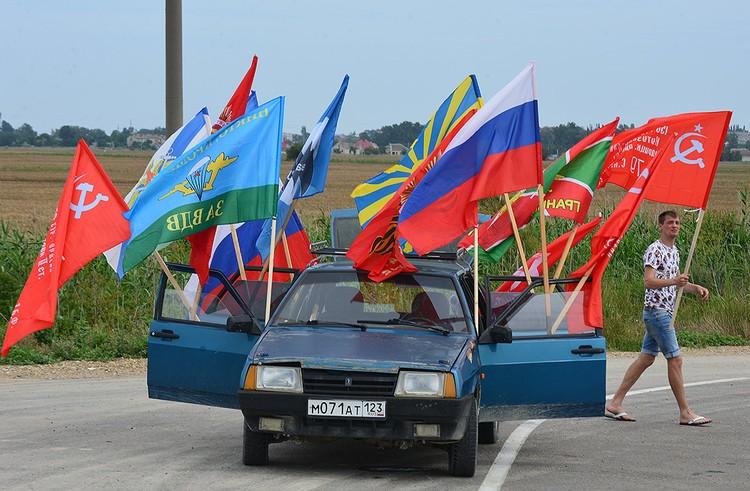 Торговля флагами у обочины трассы.