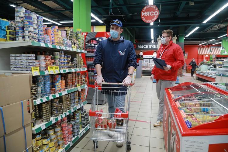 Волонтеры покупают продукты для пожилых людей.