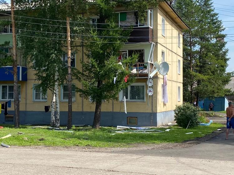 На лиственнице висит оконная рама, на земле - остатки балконного остекленения