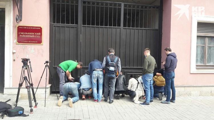 Журналисты смотрели за Мариной в щель в воротах