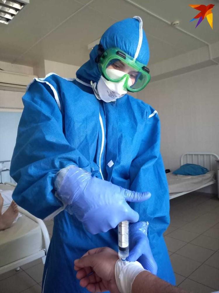 Врачи работают в коронавирсуном госпитале в специальных костюмах