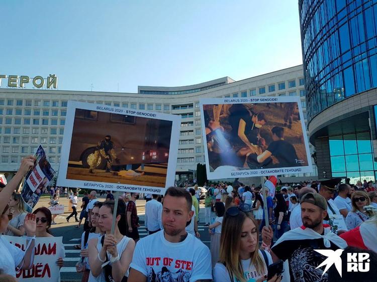 Митингующие держат плакаты с фотографиями жертва силовиков.