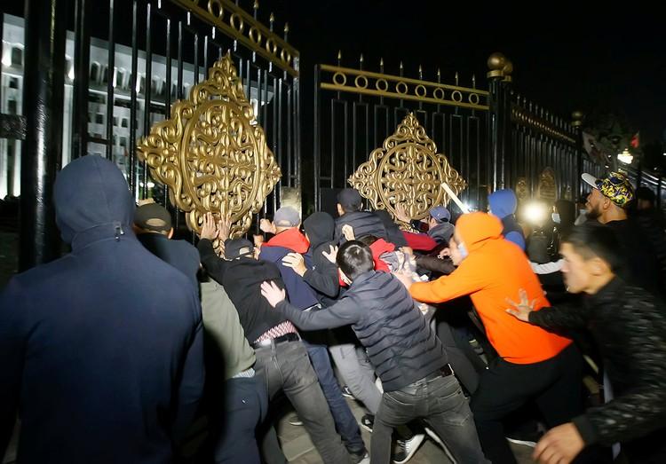 Протестующие ломают ворота у правительственного здания в Бишкеке.