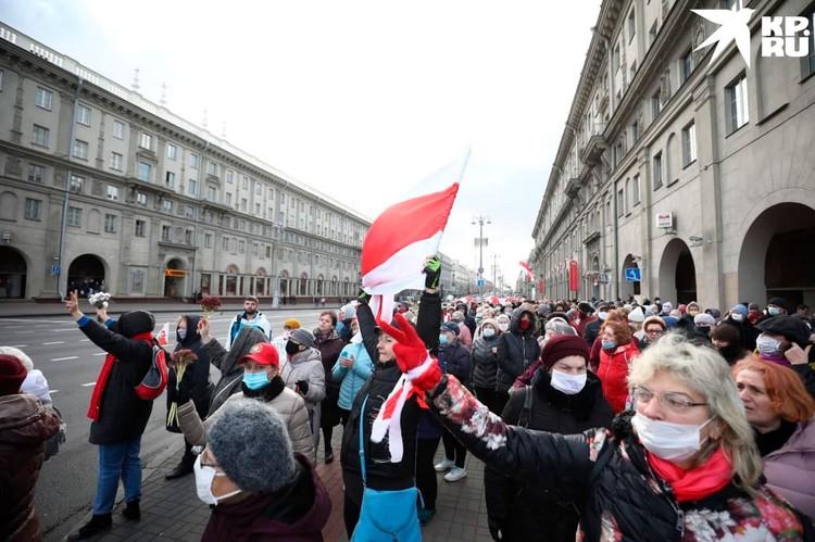 В руках у манифестантов бело-красно-белая символика белорусской оппозиции, цветы. Фото: Иван Иванов