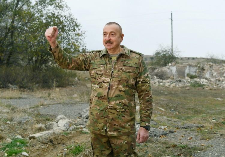 Президент Азербайджана Ильхам Алиев демонстрирует победный жест во время посещения возвращенных территорий Нагорного Карабаха.