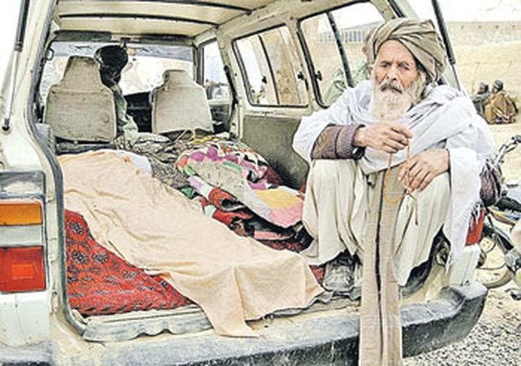 Старик афганец сидит рядом с телами его родных, застреленных во сне американским воякой. Всего от рук палача погибли 16 мирных жителей.
