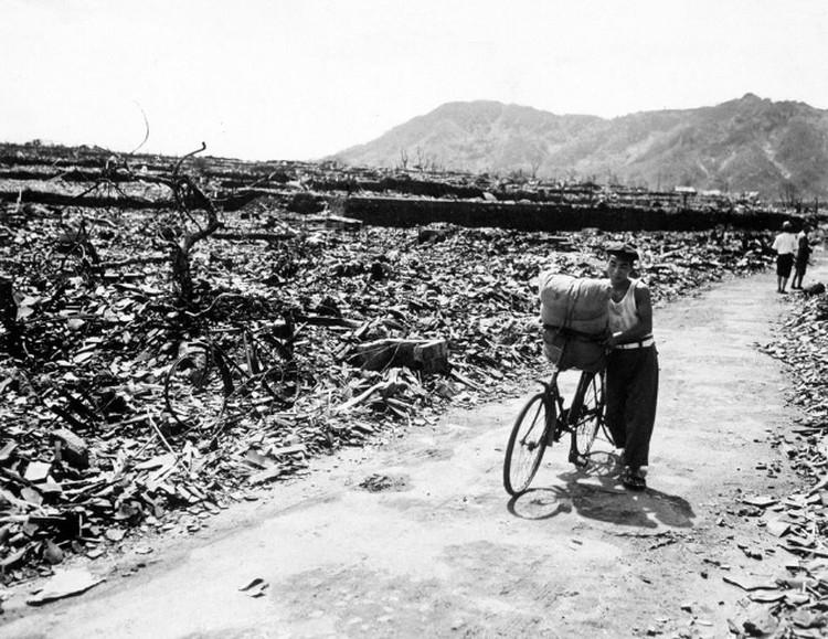 Выживший мужчина ведет нагруженный велосипед по расчищенной от руин дороге