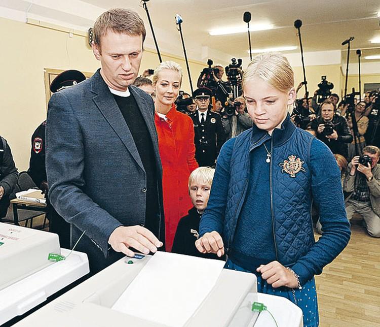 На избирательный участок  Алексей Навальный пришел  с супругой Юлией (в красном плаще), сыном Захаром и дочерью Дарьей.