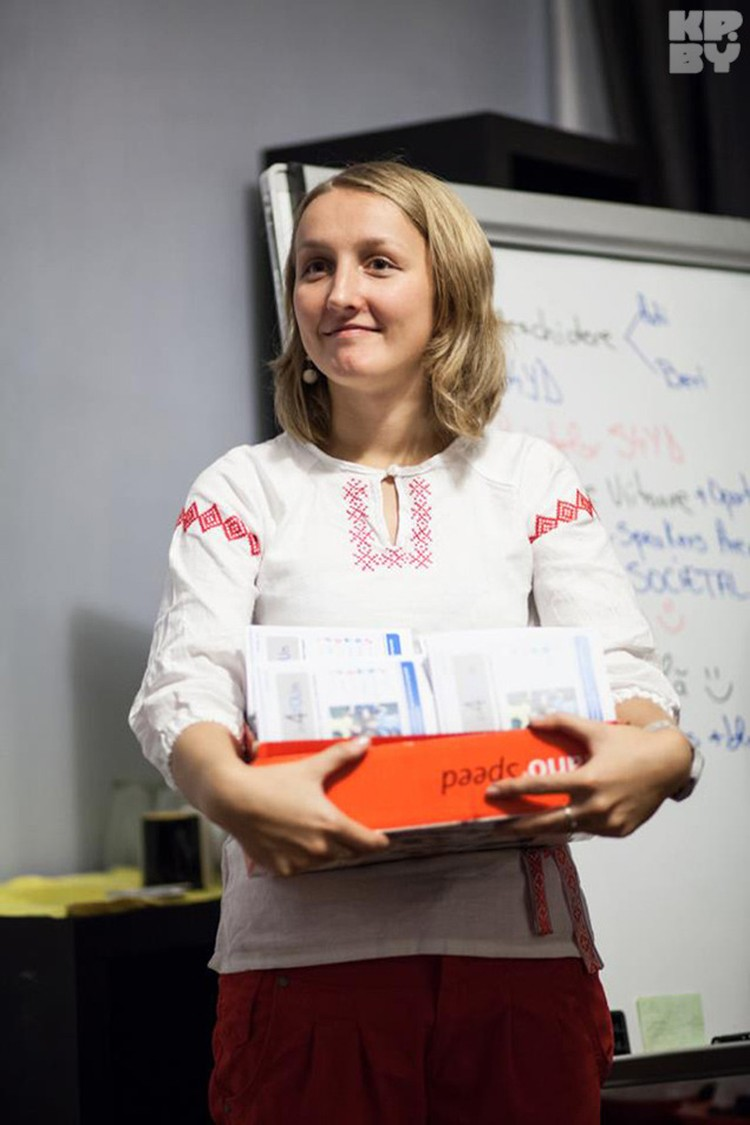 Аня на презентации проекта. В руках - брошюры, которые она делала вместе со своими студентами