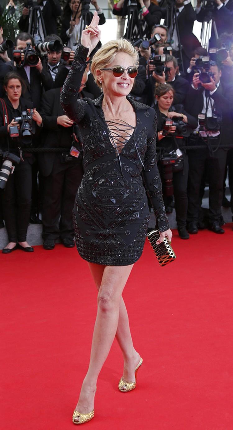 Актриса выбрала для красной дорожки короткое черное платье со шнуровкой в зоне декольте и яркие солнцезащитные очки.