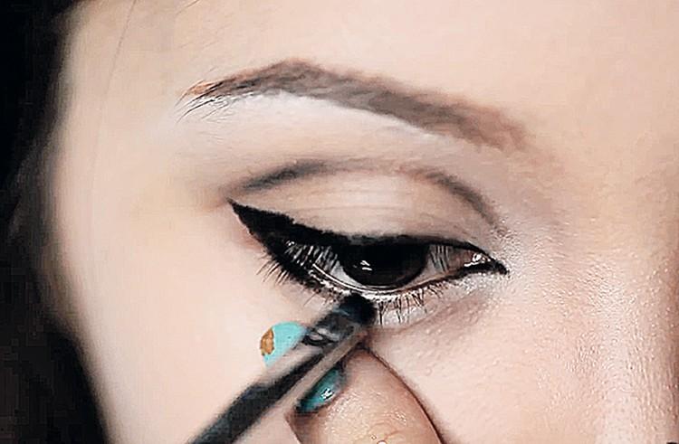 Складку над веком прорисовывает коричневым, затем черным карандашом. Наклеивает по краям глаза искусственные пучки ресниц. Водостойкой подводкой прорисовывает нижнее веко поверх ресниц.