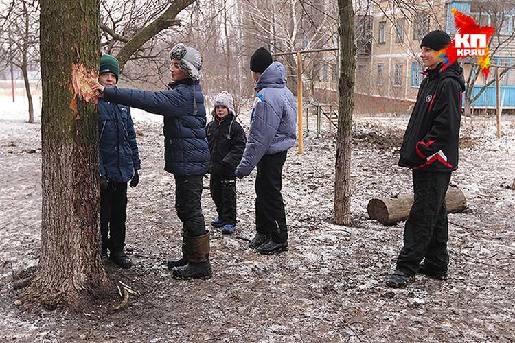 Подростки Горловки показывают место попадения осколков.